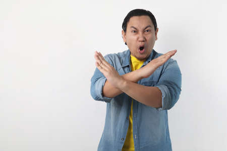 Portrait of young funy angry Asian man shows crossed arms gesture, giving warn to stop gesture, rejection concept 版權商用圖片