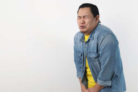 Portrait of funny Asian man crying close his eyes, gesturing as if he is having pain in his sensitive area when pee urinating