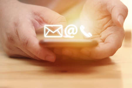 Contact us concept, man using smart phone with e-mail, mail, and phone icons graphic, selective focus