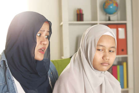 Muslim mother having bad time with her daugther, mom reprimands her teenage girl, Islamic Asian people