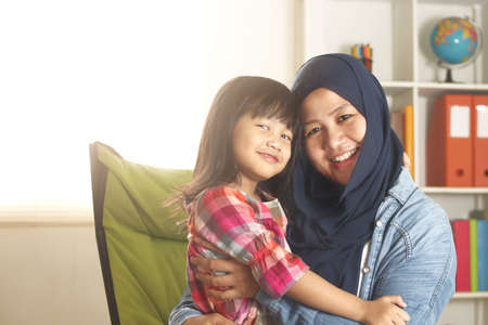 Muslim mother wearing hijab smiling while playing with her baby girl, mom and daughter love each other, happy single parent