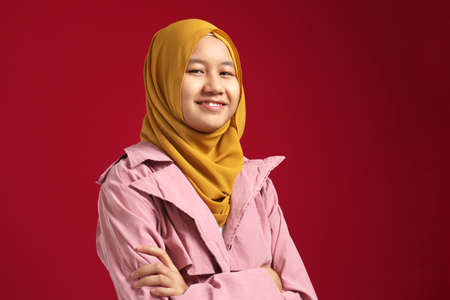 Happy smart cute young confident Asian teenage muslim girl smiling at camera with arms crossed against red background