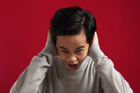 Portrait of angry Asian boy screaming loud while covering his ears, naughty rebel school student concept, isolated on red background 版權商用圖片
