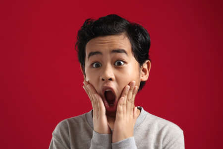 Portrait of funny young Asian boy looking at camera with open mouth and big eyes, shocked surprised expression against red background