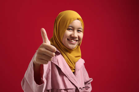 Portrait of young Asian muslim teenage girl wearing hijab shows thumbs up gesture, smiling happy face, approved OK sign, against red background 版權商用圖片
