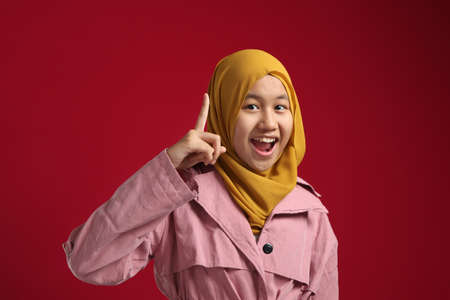 Asian muslim young teenage girl wearing hijab smiling for having good idea with finger pointing up, against red background