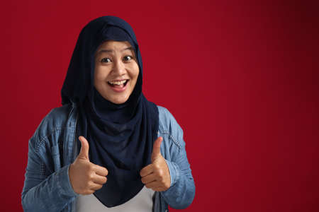Portrait of young Asian muslim lady wearing hijab shows thumbs up gesture, smiling happy face, approved OK sign, against red background