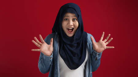 Portrait of cute young Asian muslim lady wearing hijab shows surprised or shocked expression with big eyes and open mouth, against red background 版權商用圖片
