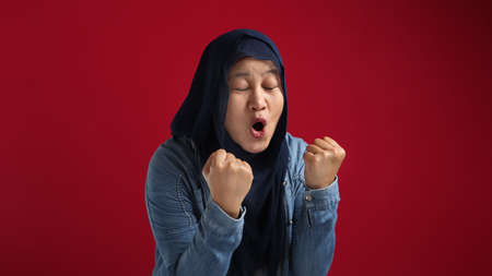 Portrait of success beautiful muslim businesswoman wearing hijab screaming shouting and shows winning victory gesture over red background