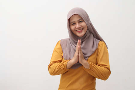 Portrait of Asian muslim lady smiling and shows greeting gesture, concept of islamic celebration of ramadan or eid fitr