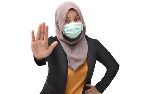 Asian muslim businesswoman wearing hijab and medica face mask shows stop hand sign gesture, isolated on white. Stop corona covid disase concept