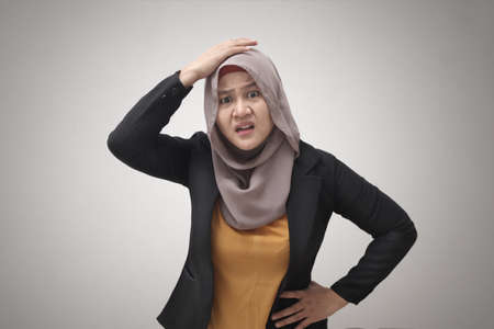 Asian muslim business woman wearing hijab looks confused and worried gesture, against gray background
