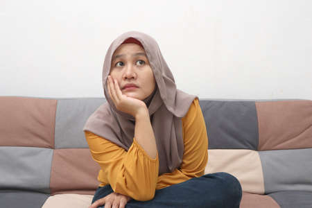 Beautiful Asian muslim woman thinking something seriously while sitting on sofa, girl with contemplation expression, looking up 版權商用圖片