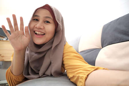 Beautiful Asian muslim lady doing selfie portrait on phone or doing video call while sitting on sofa, happy smiling cheerful expression, waving gesture 版權商用圖片