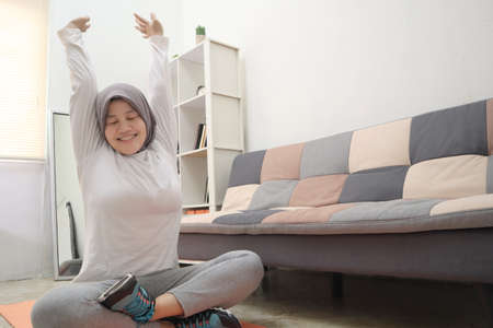 Asian muslim woman wearing hijab strecth her arms after doing exercise at home, keep healthy and fit during new normal lifestyle, indoor home workout concept