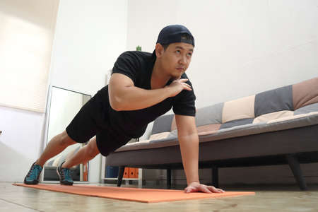 Asian male doing exercise at home to stay healthy on new normal lifestyle, indoor home workout concept, shoulder tap push ups plank position