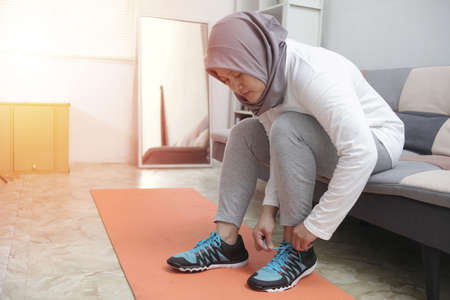 Young Asian muslim woman tying her shoelaces in her bedroom, preparing for workout, indoor home exercise concept