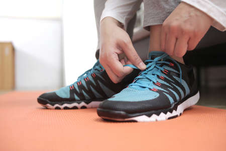 Young woman tying her shoelaces in her bedroom, preparing for workout, indoor home exercise concept, close up image
