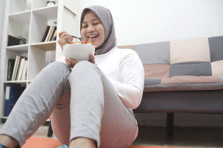 Asian muslim woman wearing hijab eating healthy food, green veggies salad, after exercise at home, keep healthy and fit during new normal lifestyle concept