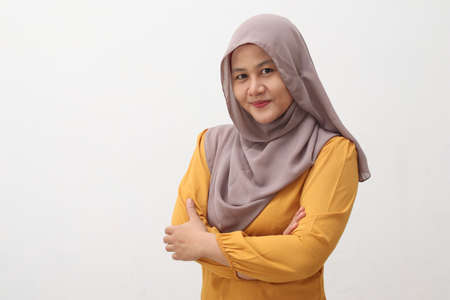 Portrait of Asian muslim woman wearing hijab smiling friendly with crossed arms, confident gesture, successful businesswoman, isolated on white