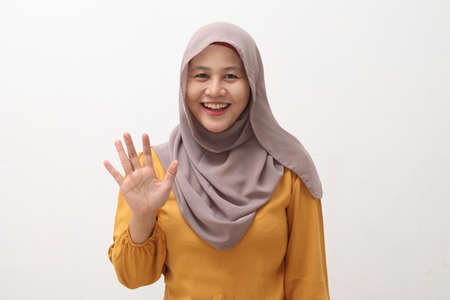 Happy cheerful beautiful Asian muslim lady wearing hijab waving to camera, doing selfie or video call gesture, isolated on white