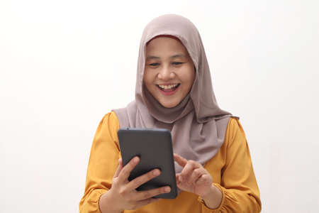 Muslim business woman wearing hijab holds and using smart phone or digital tablet. Successful businesswoman entrepreneur and internet gadget concept, isolated on white