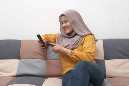 Beautiful Asian muslim woman using phone while sitting on sofa, girl doing chat text message on smartphone and smiling