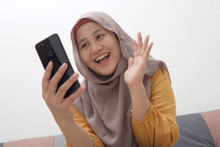 Closeup of Asian muslim woman using a smart phone. Happy smiling gesture having good news when communicating on internet online, video call, selective focus