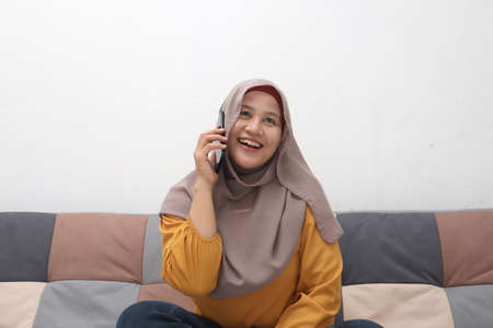 Beautiful Asian muslim woman using phone while sitting on sofa, girl talking on smartphone and smiling, happy cheerful expression
