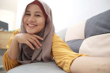 Beautiful Asian muslim lady doing selfie portrait on phone or doing video call while sitting on sofa, happy smiling cheerful expression
