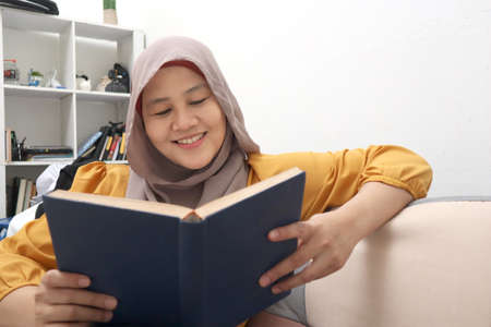 Beautiful Asian muslim woman reading book while sitting on sofa, girl enjoys her time by doing leisure activity, happy cheerful expression 版權商用圖片