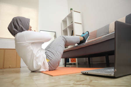Asian muslim woman wearing hijab doing abdominals exercise at home, keep healthy and fit during new normal lifestyle, indoor home workout concept