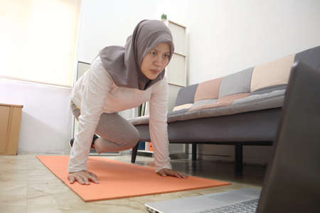 Asian muslim woman wearing hijab doing exercise at home while watching online video instruction on laptop, indoor home workout concept, keep healthy on new normal lifestyle