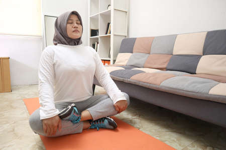 Asian muslim woman wearing hijab doing exercise at home, keep healthy and fit during new normal lifestyle, indoor home workout concept