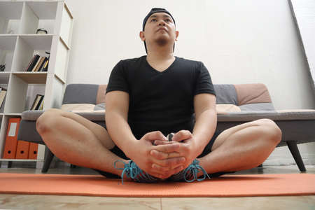 Asian male doing exercise at home to stay healthy on new normal lifestyle, indoor home workout concept, stretching for flexibility 版權商用圖片