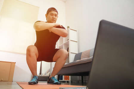Asian male doing exercise at home while watching online video instruction on laptop, indoor home workout concept, keep healthy on new normal lifestyle 版權商用圖片