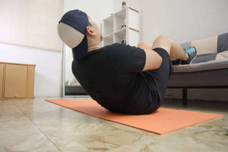 Asian male doing exercise at home to stay healthy on new normal lifestyle, indoor home workout concept, core abs abdominals training