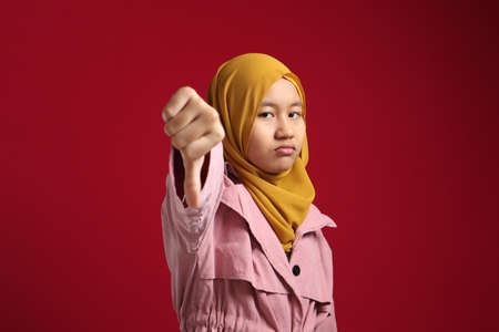Portrait of teenage asian muslim girl looked disappointed while showing thumbs down gesture, against red background Foto de archivo