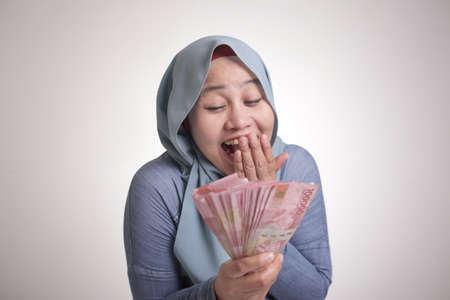 Portrait of Indonesian muslim woman holding rupiah money, smiling laughing winning gesture