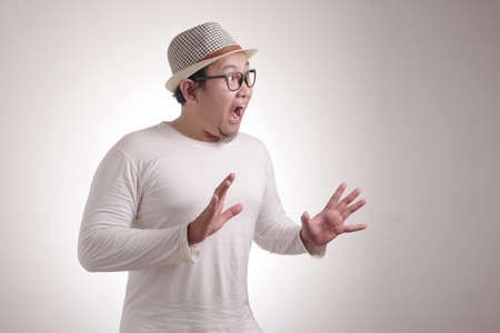 Portrait of young Asian man shocked to see something on his side, excited gesture with copy space Banque d'images