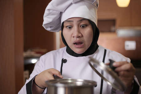 Asian female chef open cooking pot and smelling food aroma that she cooked, failure in cooking concept, bad worried face expression