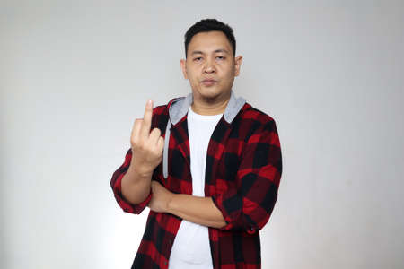 Portrait of angry Asian man shows middle finger rude gesture, looking at camera