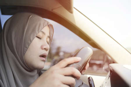 Female Asian muslim driver sleeping while driving a car, dangerous traffic safety accident crash car insurance concept