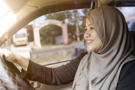 Portrait of young Asian muslim woman smiling and driving a car, good looking entrepreneur, car sharing concept