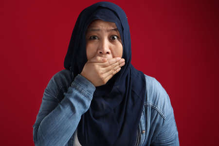 Close up portrait of Asian muslim woman wearing hijab closing her mouth with fingers. Worried gesture, can't say anything. Shocked surprised to hear bad news or gossip
