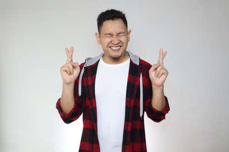Portrait of Asian man close his eyes smiling and cross fingers, making promise gesture