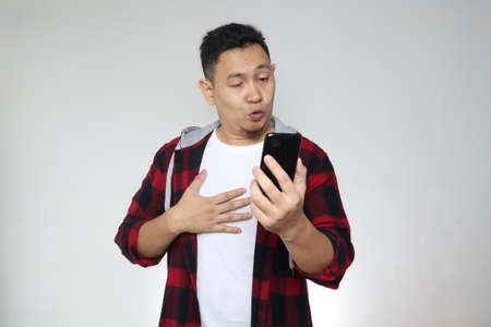 Portrait of young funny Asian man looking at his phone with naughty expression, found