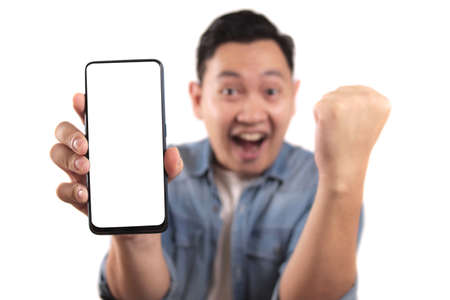 Portrait of young young Asian man presenting smart phone mockup with happy cheerful expression, winning gesture