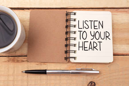 Listen to your heart, text words typography written on book against wooden background, life and business motivational inspirational concept