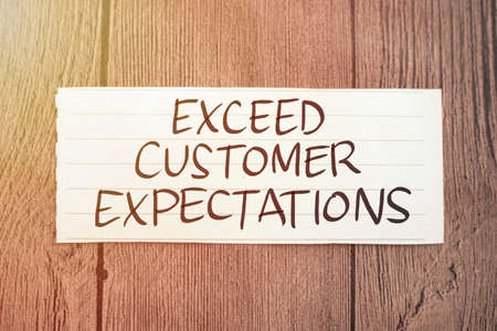 Exceed customer expectations, text words typography written on paper against wooden background, life and business motivational inspirational concept
